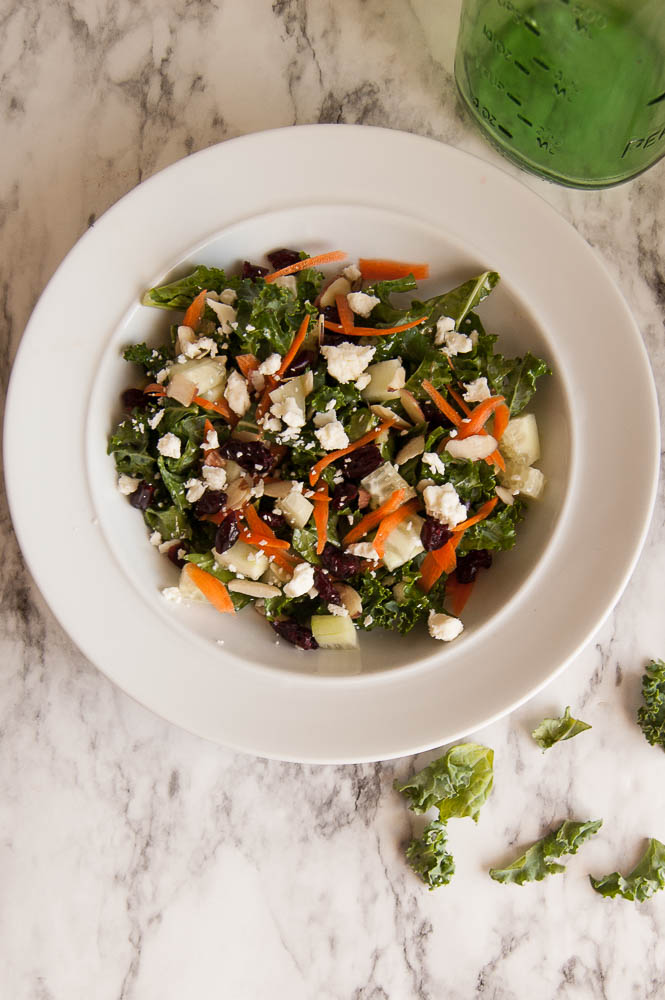 Cranberry Almond Kale salad with dried cranberries, sliced almonds, cucumbers, feta and a lemon-garlic dressing